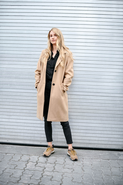 Anna Gasser, oblečena v bež plašč in naslonjena na garažna vrata.