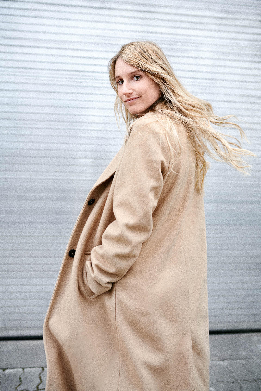 Fotografija Anne Gasser, na kateri s pogledom čez ramena strmi v fotoaparat.