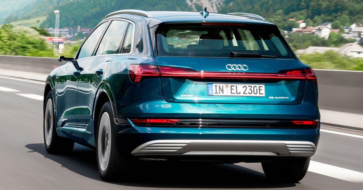 Vozilo Audi e-tron med vožnjo na avtocesti. V ozadju hribi in gozd.