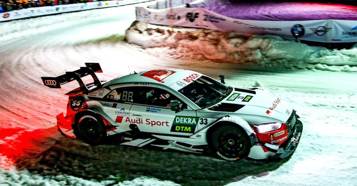 Športno vozilo Audi med zavojem na snežni progi. Dirka je ponoči.