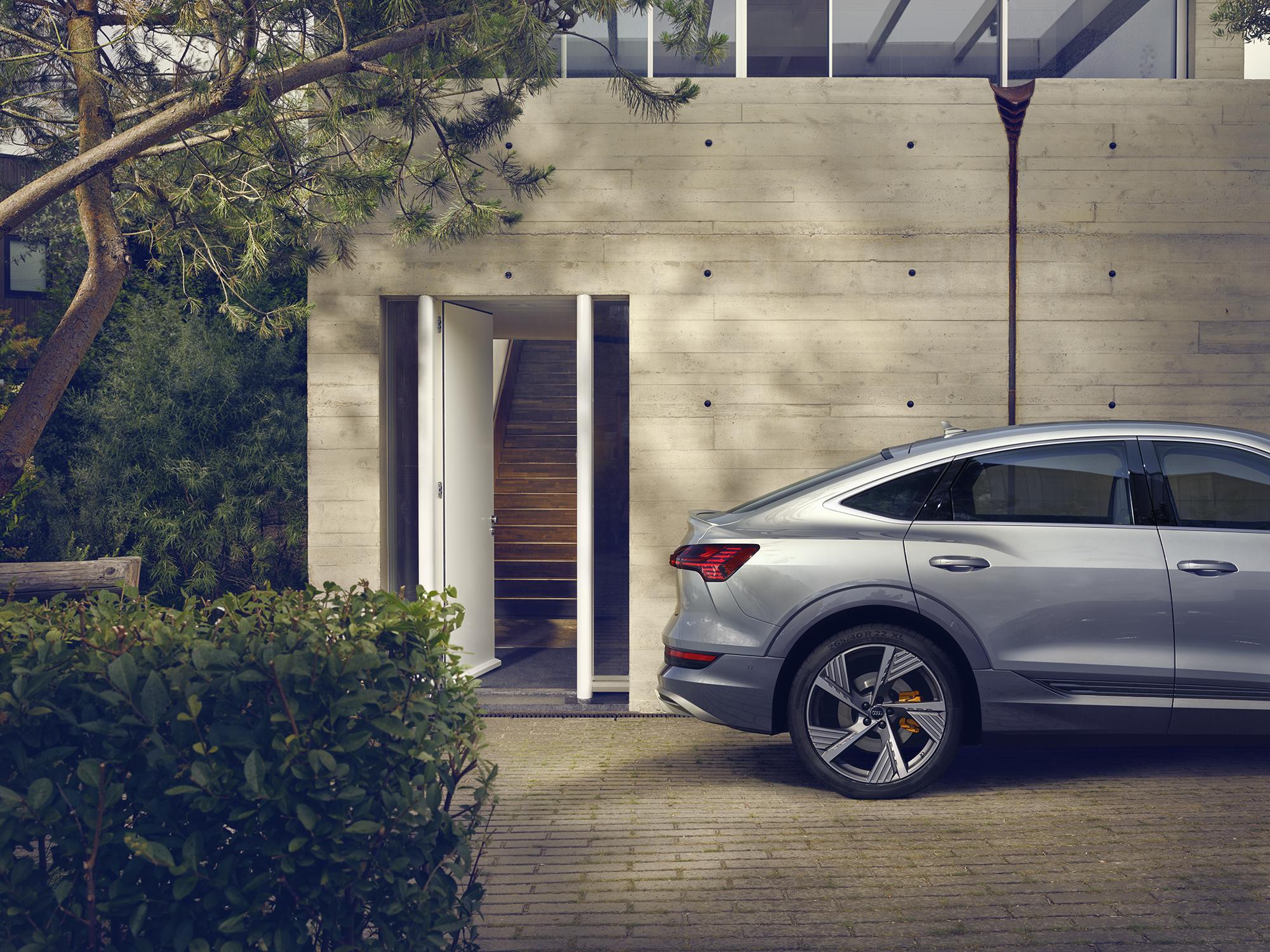 Audi e-tron sportback pred moderno betonsko hišo, na kateri so odprta vhodna vrata