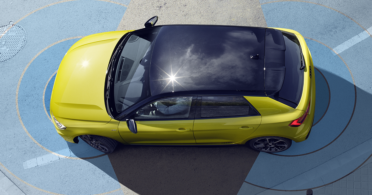 Rumeno vozilo Audi na parkirnem mestu, kjer sta narisana dva modra polkroga