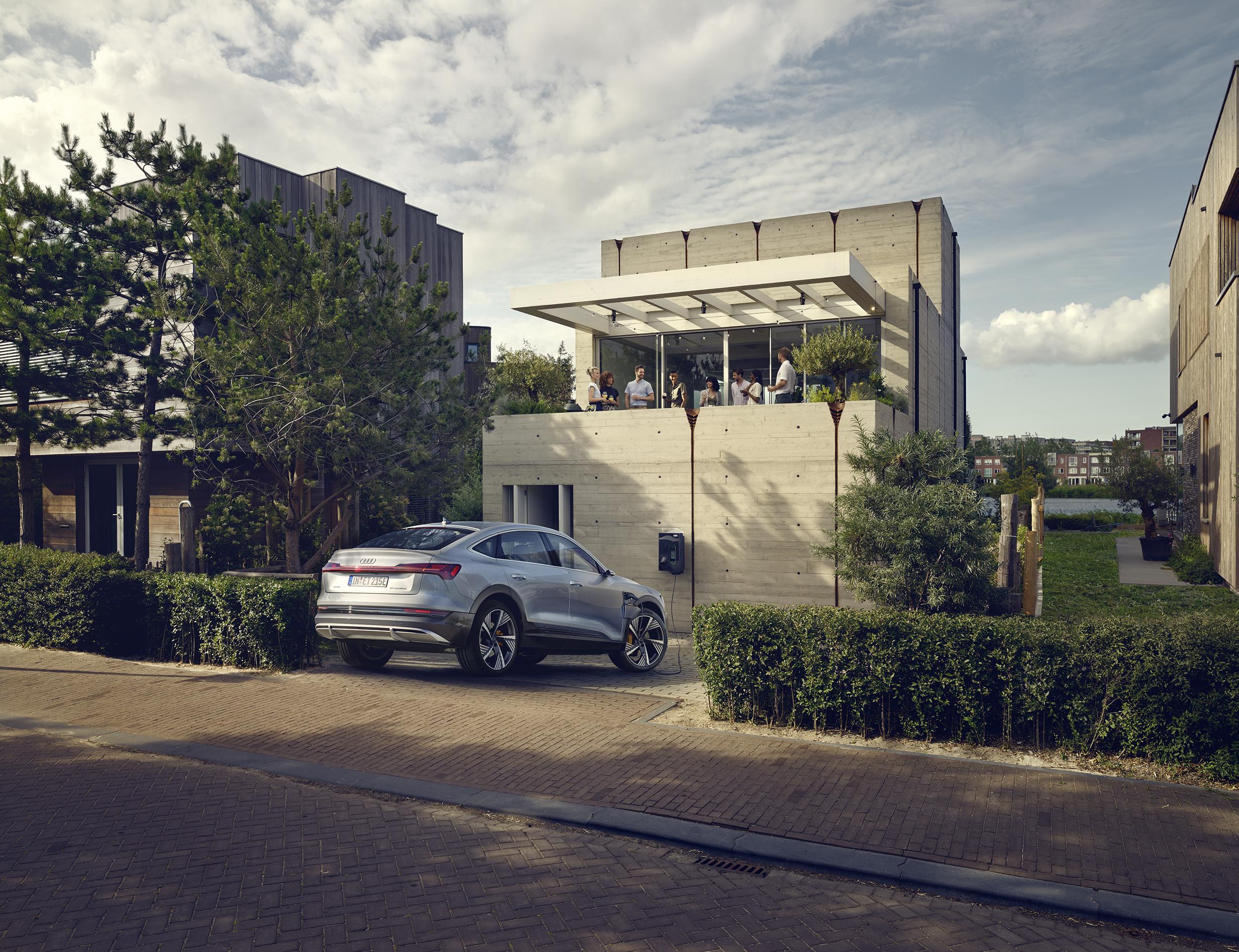 Audi e-tron sportback parkiran pred moderno betonsko hišo. Na terasi hiše več ljudi, v okolici veliko zelenja