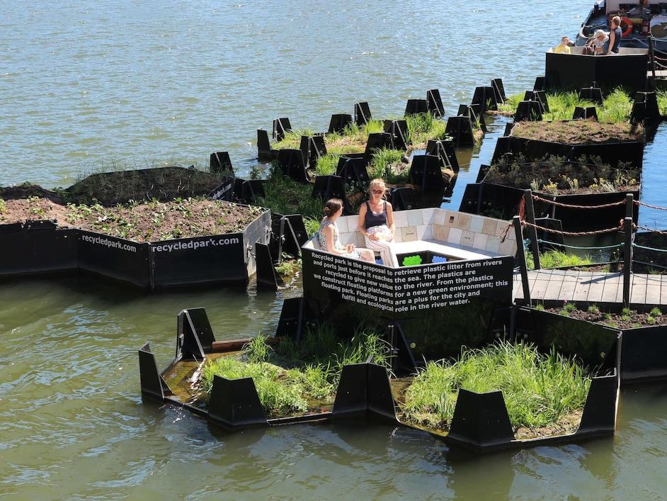 Dve ženski, ki sedita na klopi na malih otokih iz recikliranih materijalov sredi reke