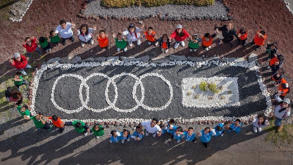 Slika ljudi, ki stojijo ob Audi znaku narejenem iz kamna. Slikano od zgoraj