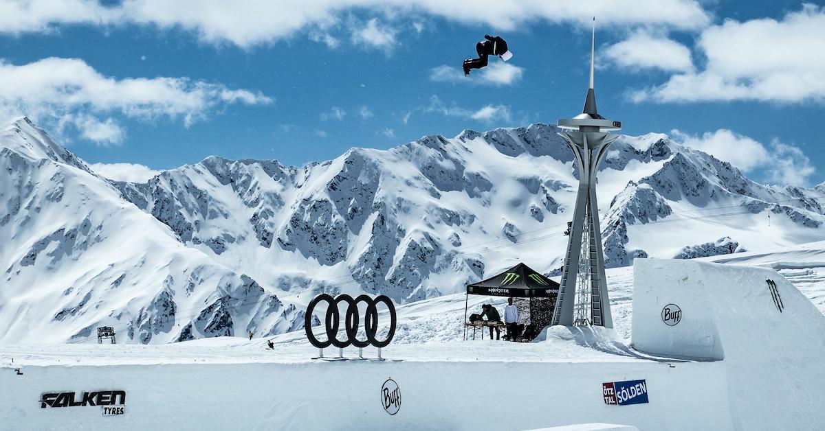 Deskar na snegu med skokm na skakalnici, čez Audi znak. V ozadju zasnežene gore in modro nebo.