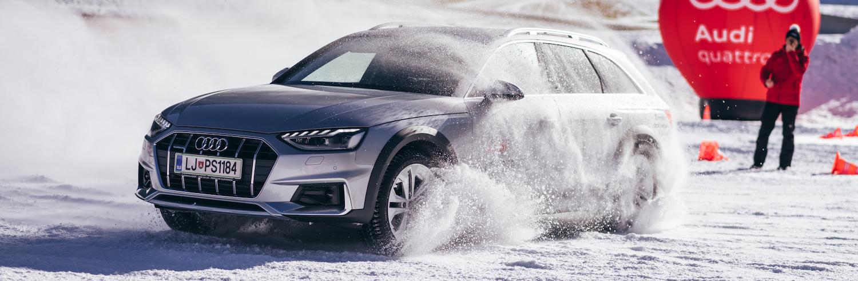 Audi vozilo med vožnjo na snežnem poligonu. Avto je v oblaku snega, v ozadju je balon Audi in v rdeče oblečen človek, ki govori po radijski postaji.