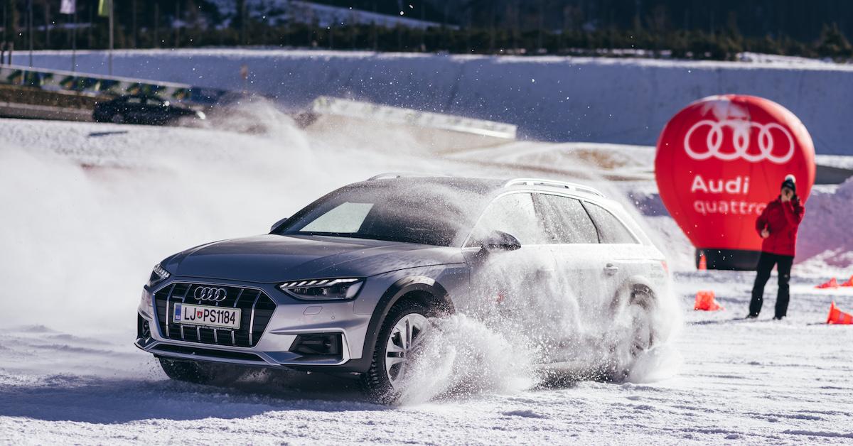 Avtomobil Audi med vožnjo na snežni progi. Avto je v oblaku prahu med zavojem. V ozadju človek in Audi rdeča zastava.
