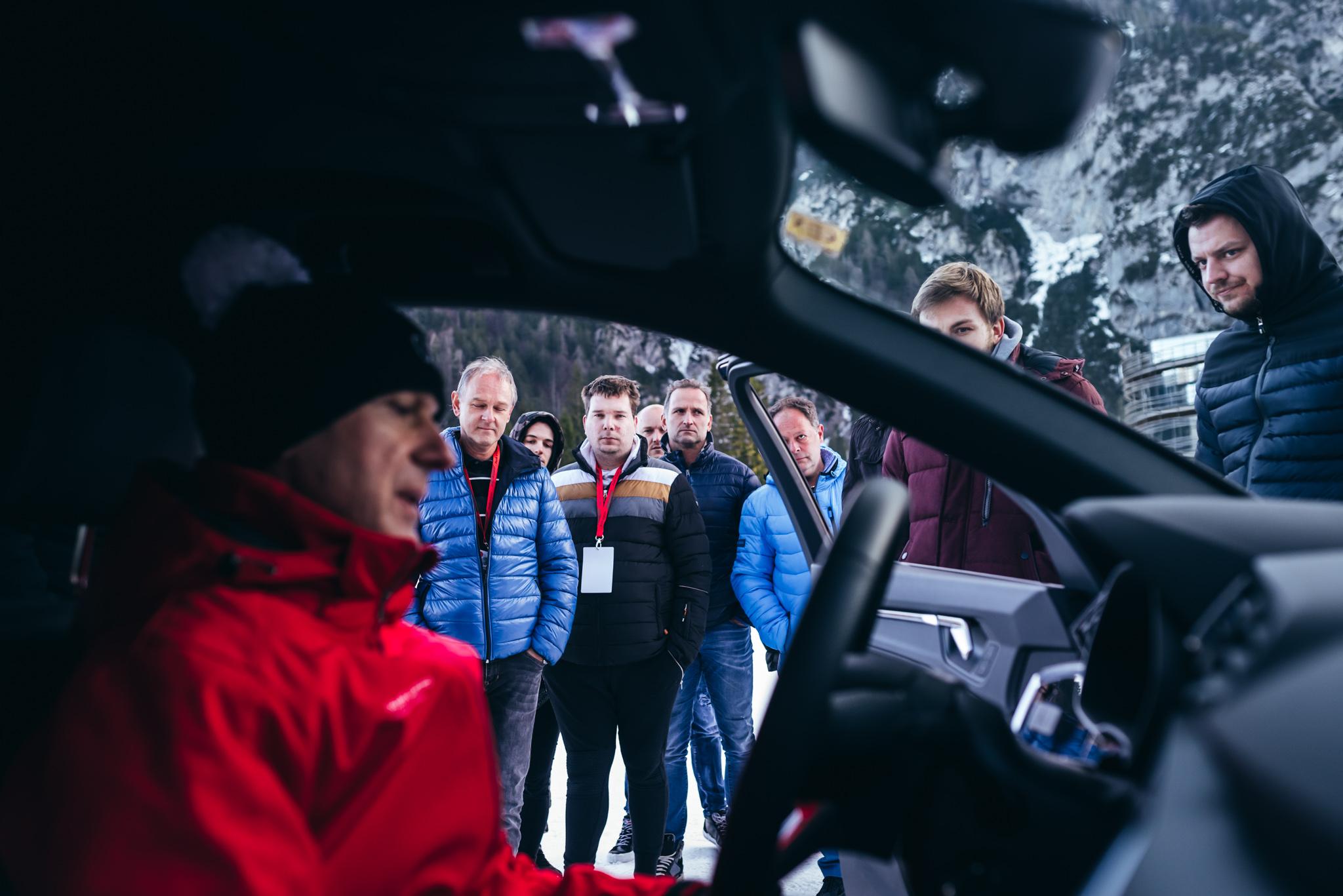 Voznik Audija sedi za volanom, in govori z udeleženci Audijevega dogodka.