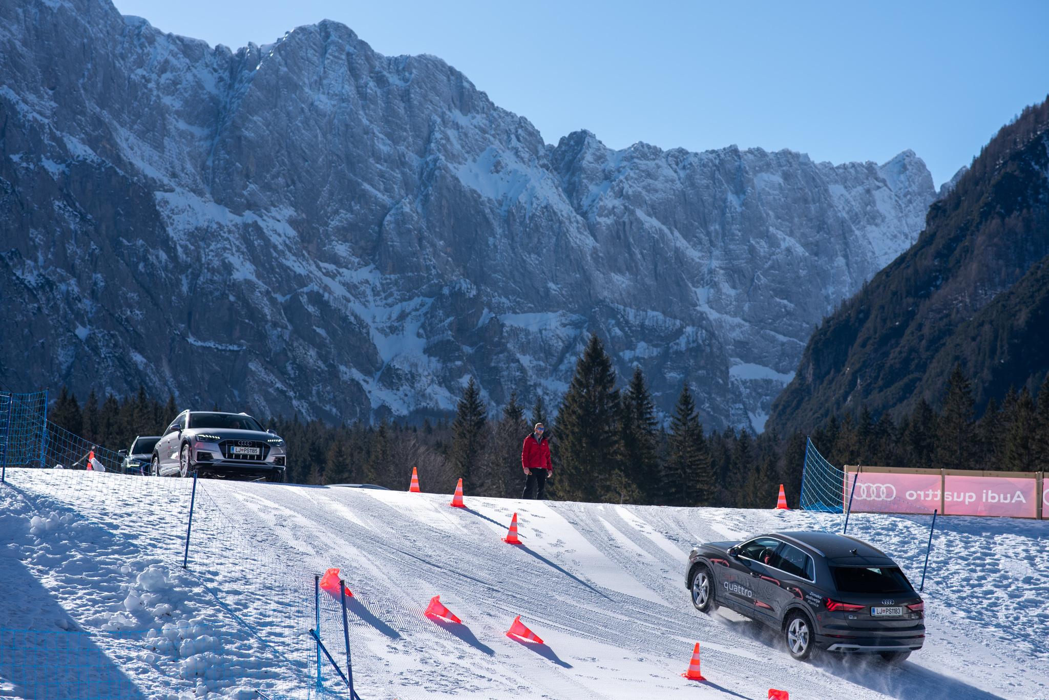 Audi quattro vozilo med vzpenjanjem po snežnem klancu, v ozadju že eno vozilo, ki se pripravlja na spust po klancu. V ozadju zasnežene gore.