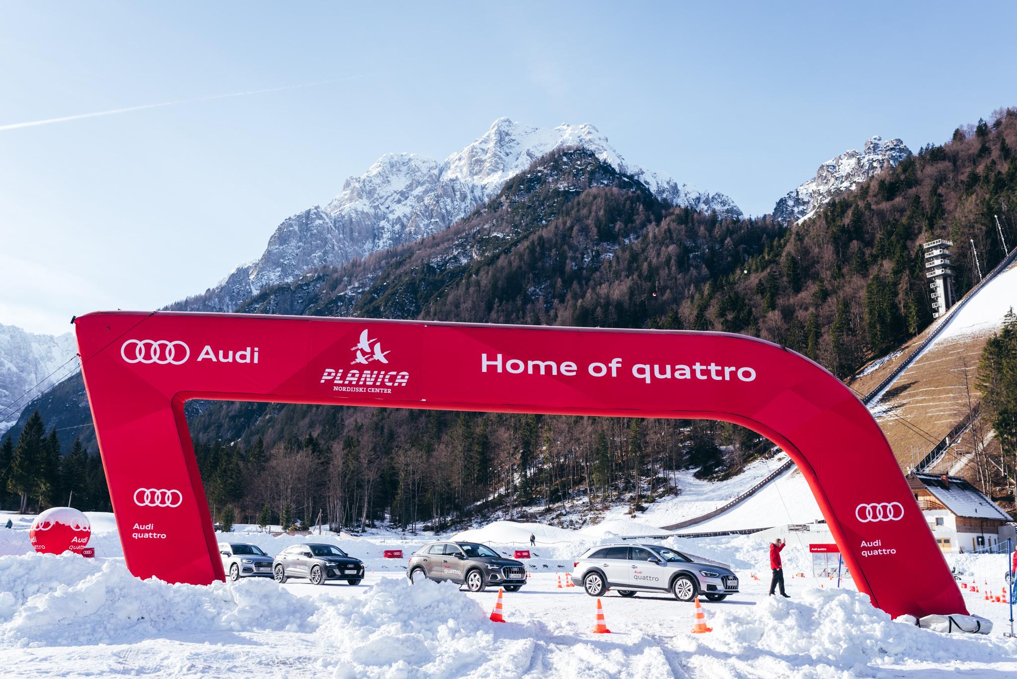 Štiri Audi vozila, pod rdečim obokom na snegu. V ozadju drevesa in zasnežene gore.