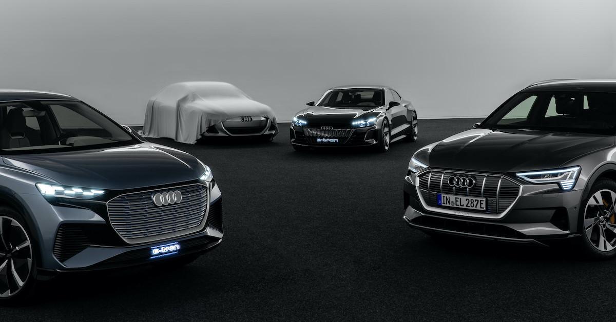 Štiri temna Audi vozila v temnem prostoru. V ozadju je en avto pokrit s pokrivalom.