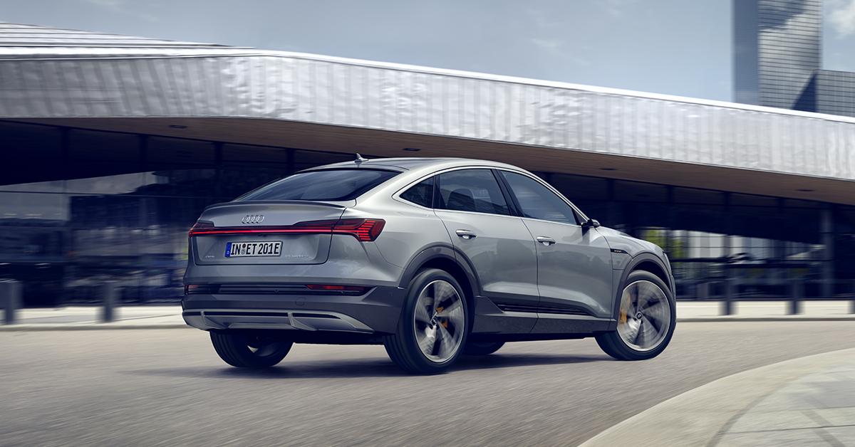 Audi e-tron sportback med vožnjo. V ozadju sodobne zgradbe in mesto.