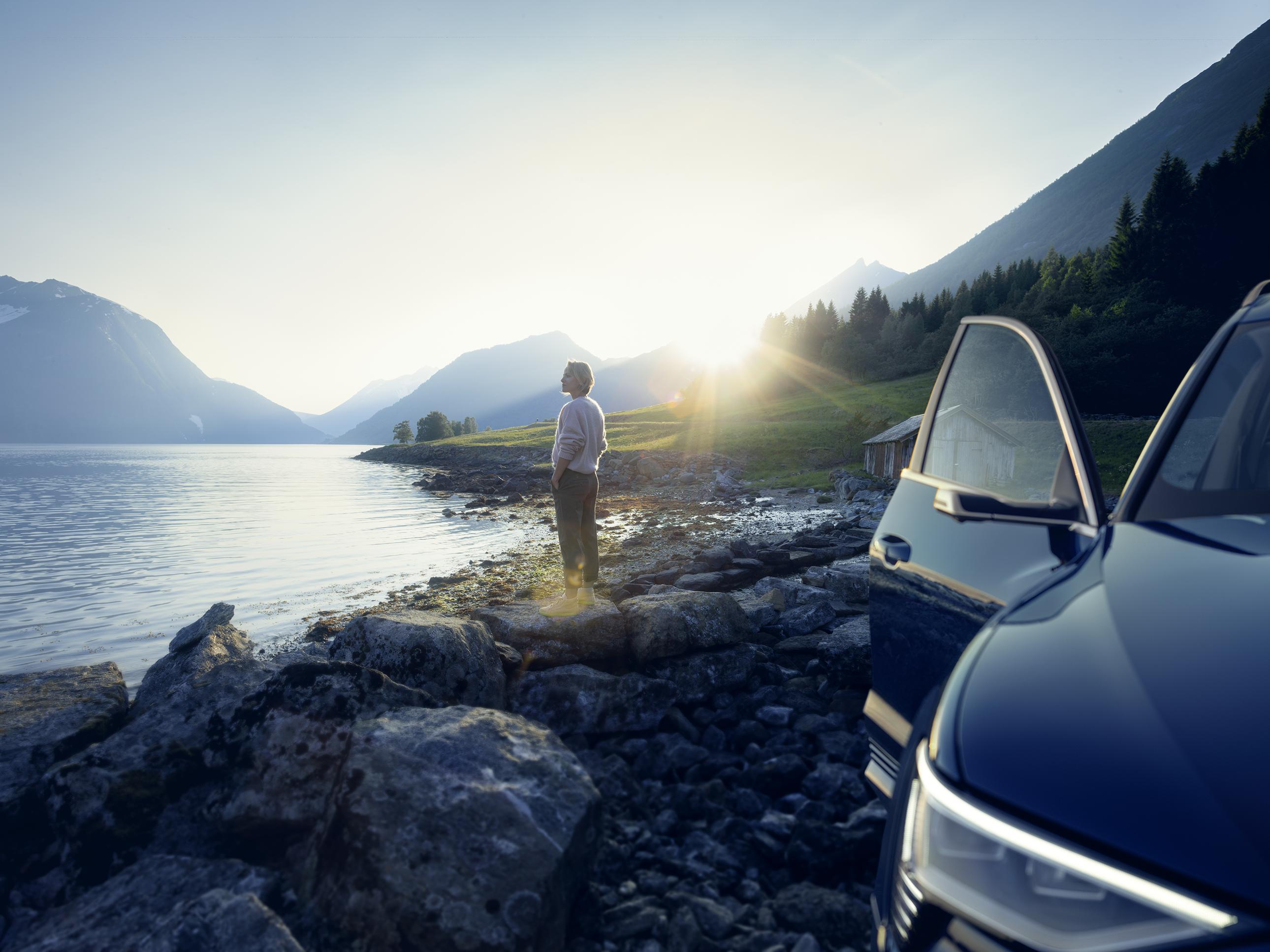 Audi e-tron na robu jezera ob sončnem vzhodu. V ozadju ženska, ki pogleduje čez jezero, ki je tudi na sliki.