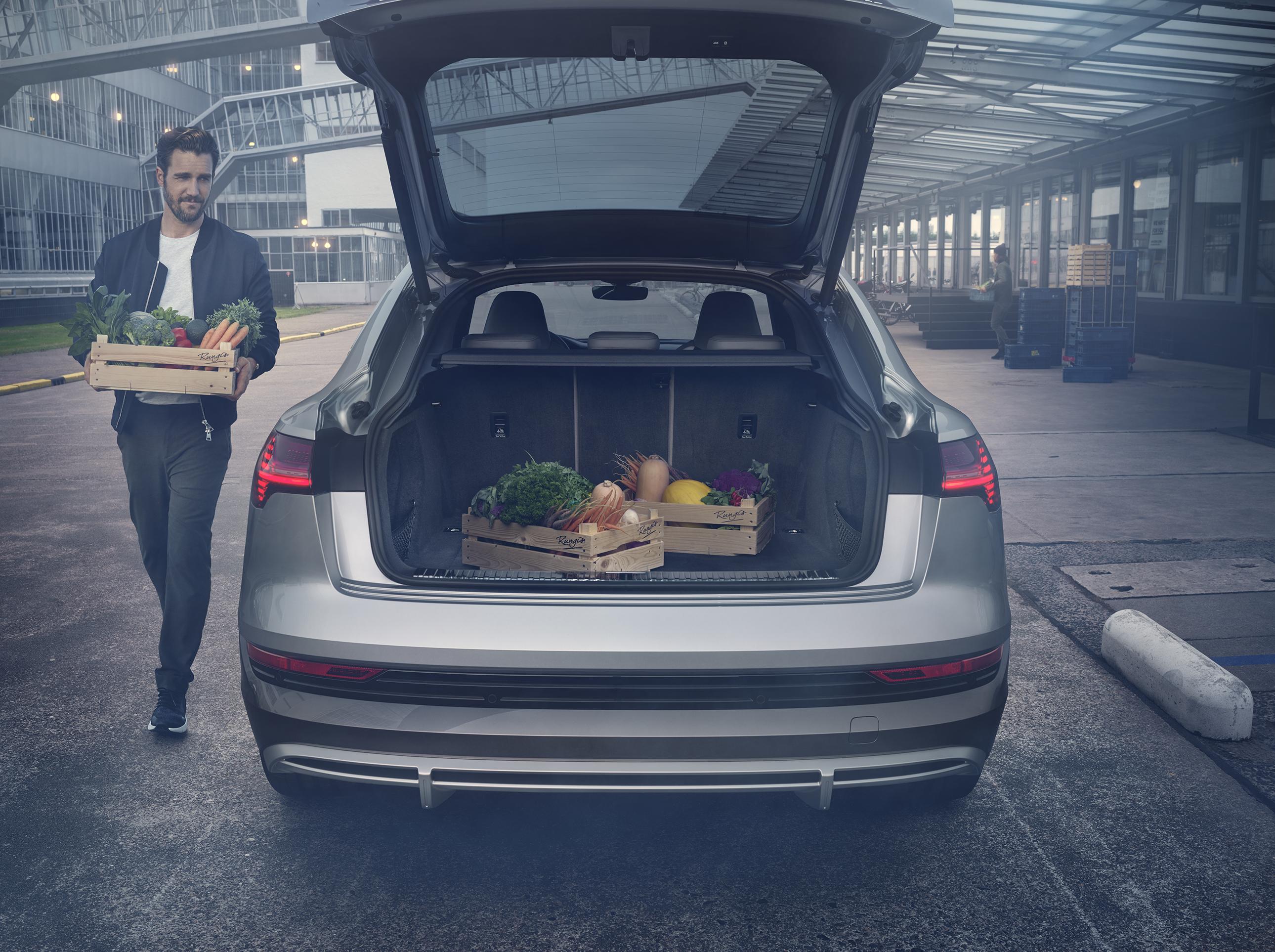 Audi e-tron sportback z odprtim prtljažnikom, v katerega moški nalaga zaboje zelenjave. Slikano v mestu