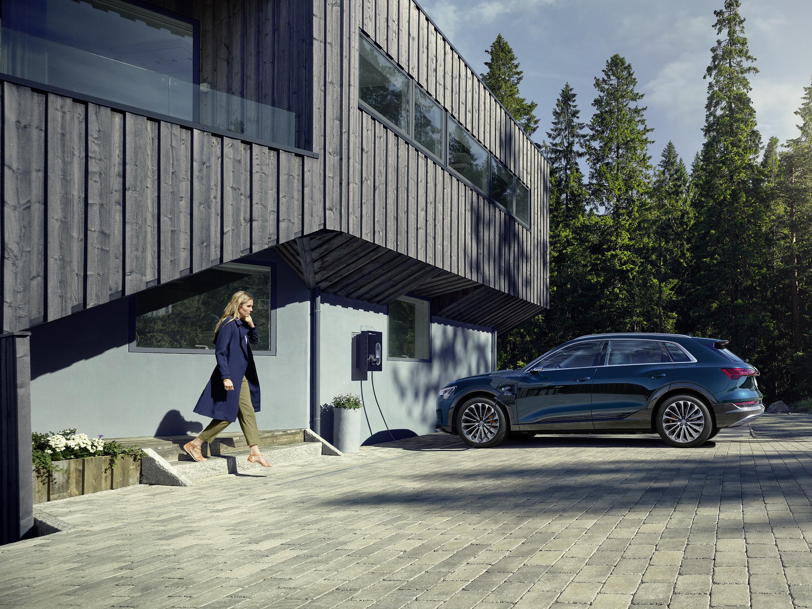 Audi e-tron pred hišo, iz katere izstopa ženska. V ozadju zelena drevesa.
