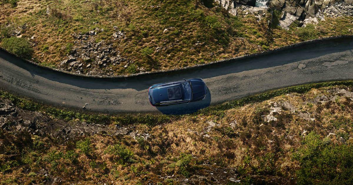 Modro vozilo Audi na podeželjski cesti. Ob cesti trava in nizko rastje