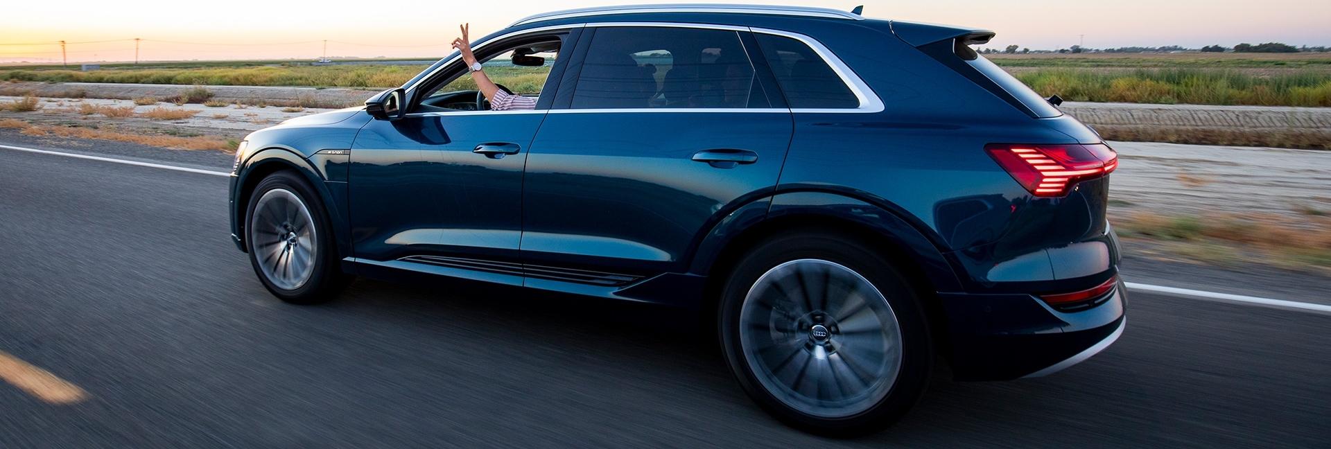 Audi e-tron na cesti, na podeželju. Voznik steguje roko čez okno.