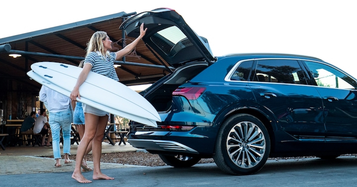 Ženska pospravlja surf desko v Audi e-tron