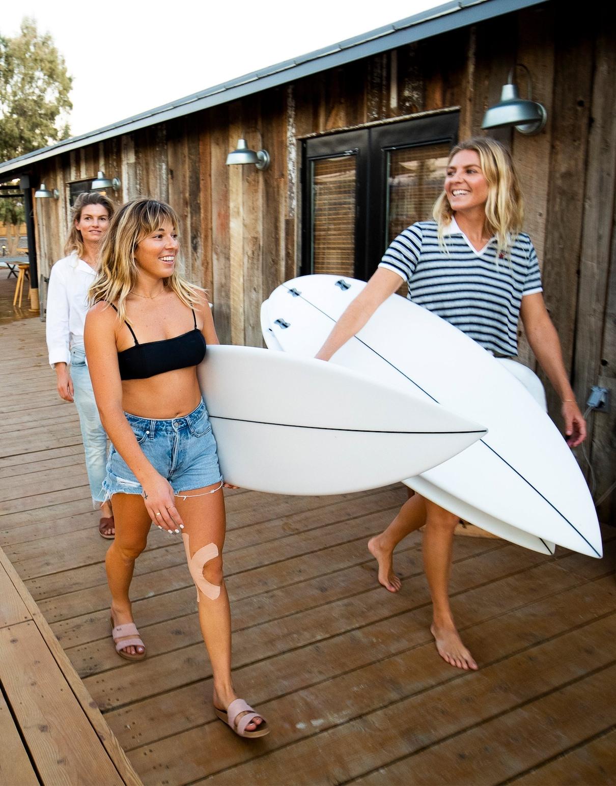 Tri ženske med hojo, v rokah nosijo surf deske