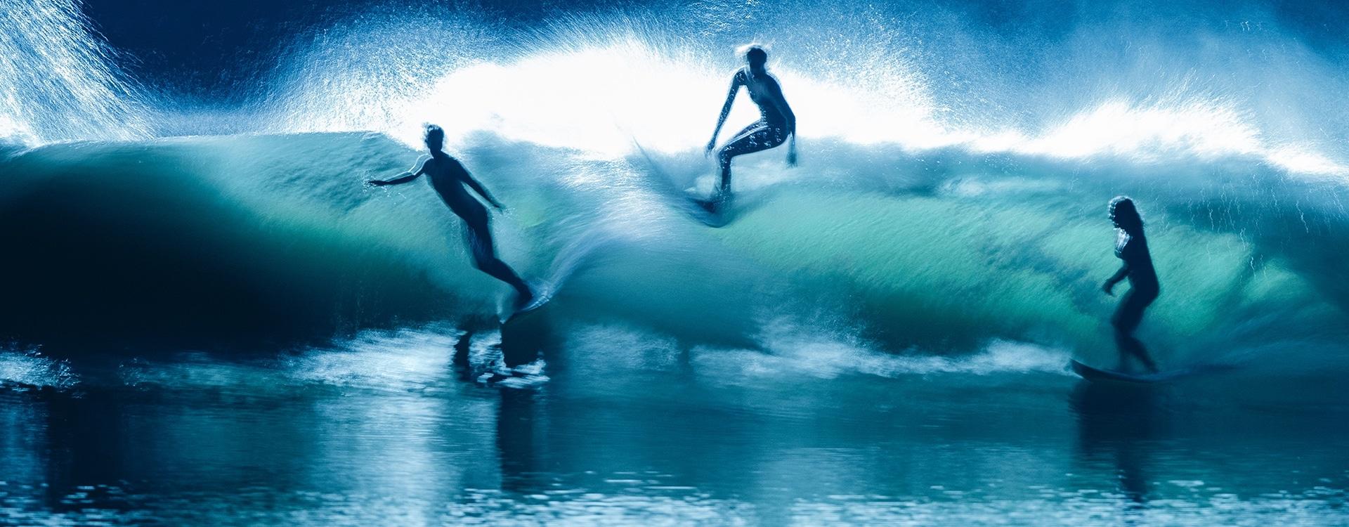 Futuristična slika treh surferjev med nočnim surfanjem