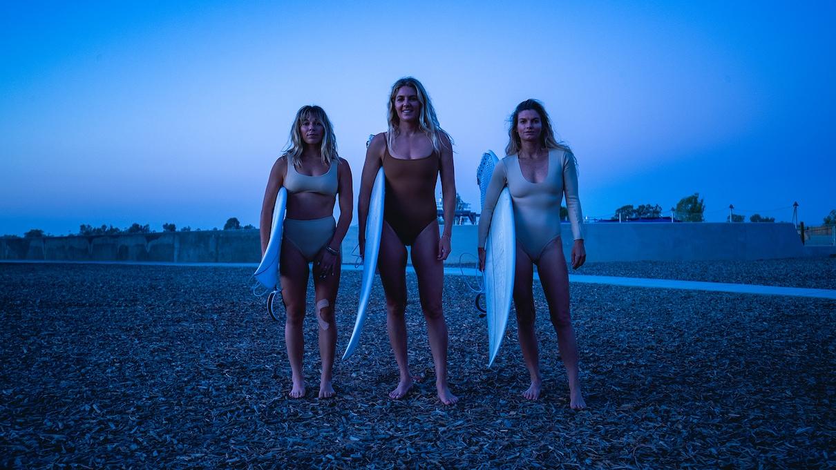 Tri ženske v kopalkah stojijo in držijo surf deske