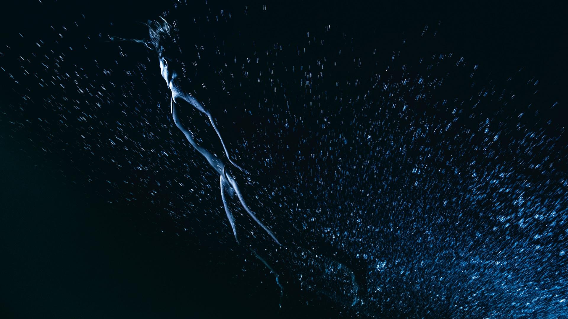 Abstraktna slika ženske, ki plava pod gladino morja