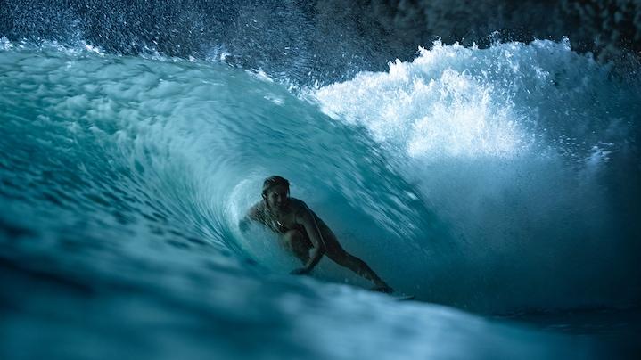 Ženska med surfanjem velikega vala ponoči