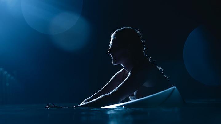 Ženska počiva na pol v vodi, na pol na surf deski. Ozadje je črno