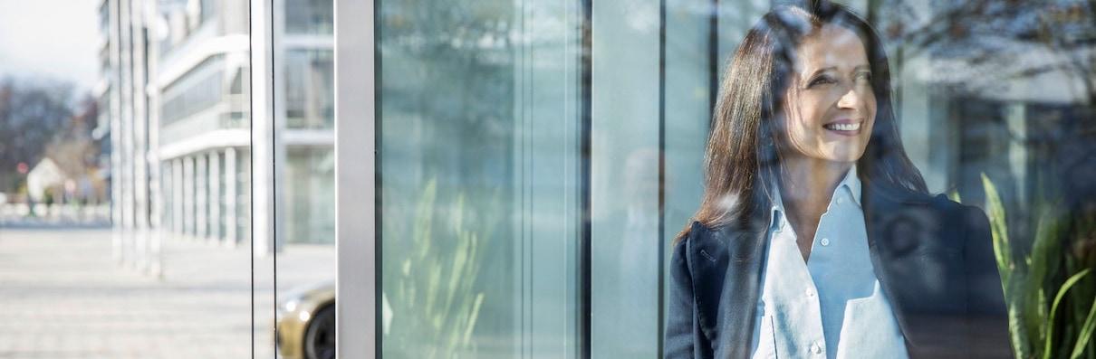 Ženska, ki gleda skozi stekleno okno. Zadaj velika moderna betonsko/steklena zgradba
