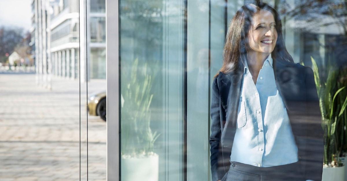Ženska pogleduje skozi veliko stekleno okno