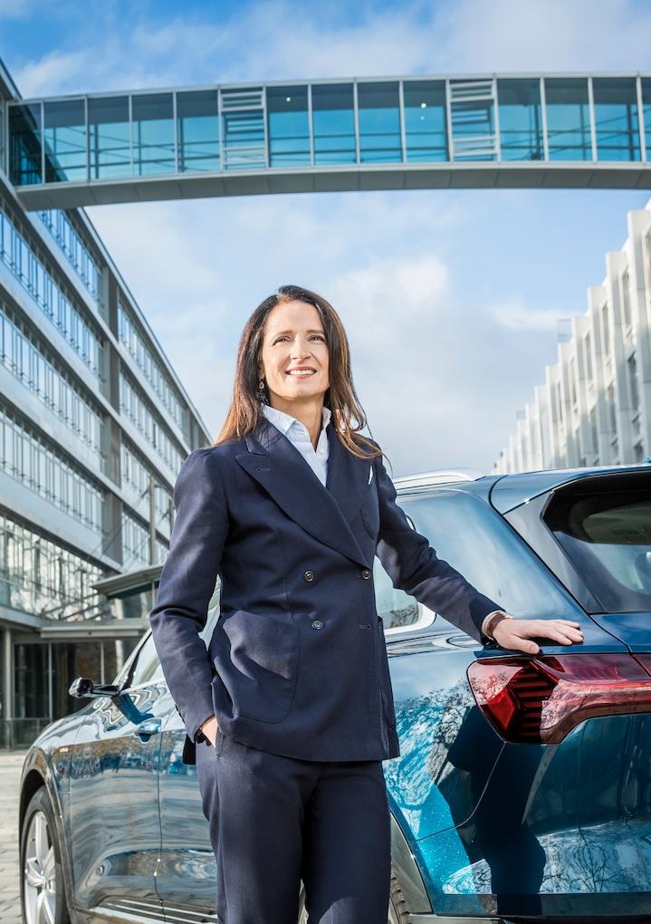 Ženska stoji pred vozilom Audi, v ozadju steklena zgradba