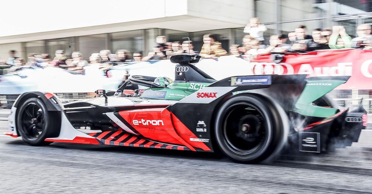 Audi dirkalno vozilo med tekmovanjem na stezi. V ozadju gledalci in bela stavba.