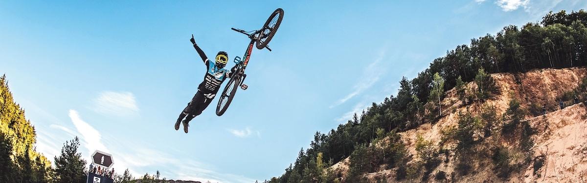 Gorski kolesar spusti kolo med skokom. V ozadju hrib in modro nebo