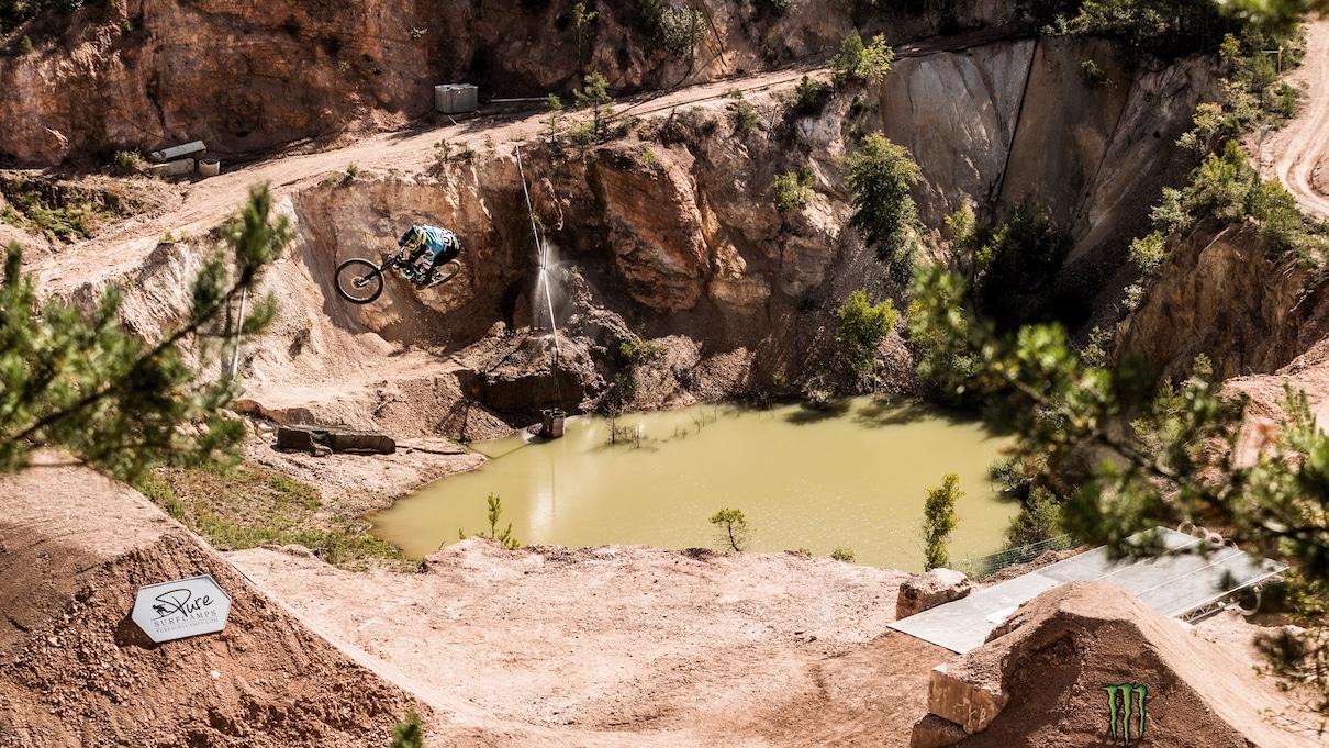 Kolesar med skokom na veliki skakalnici. V ozadju majhno jezero.