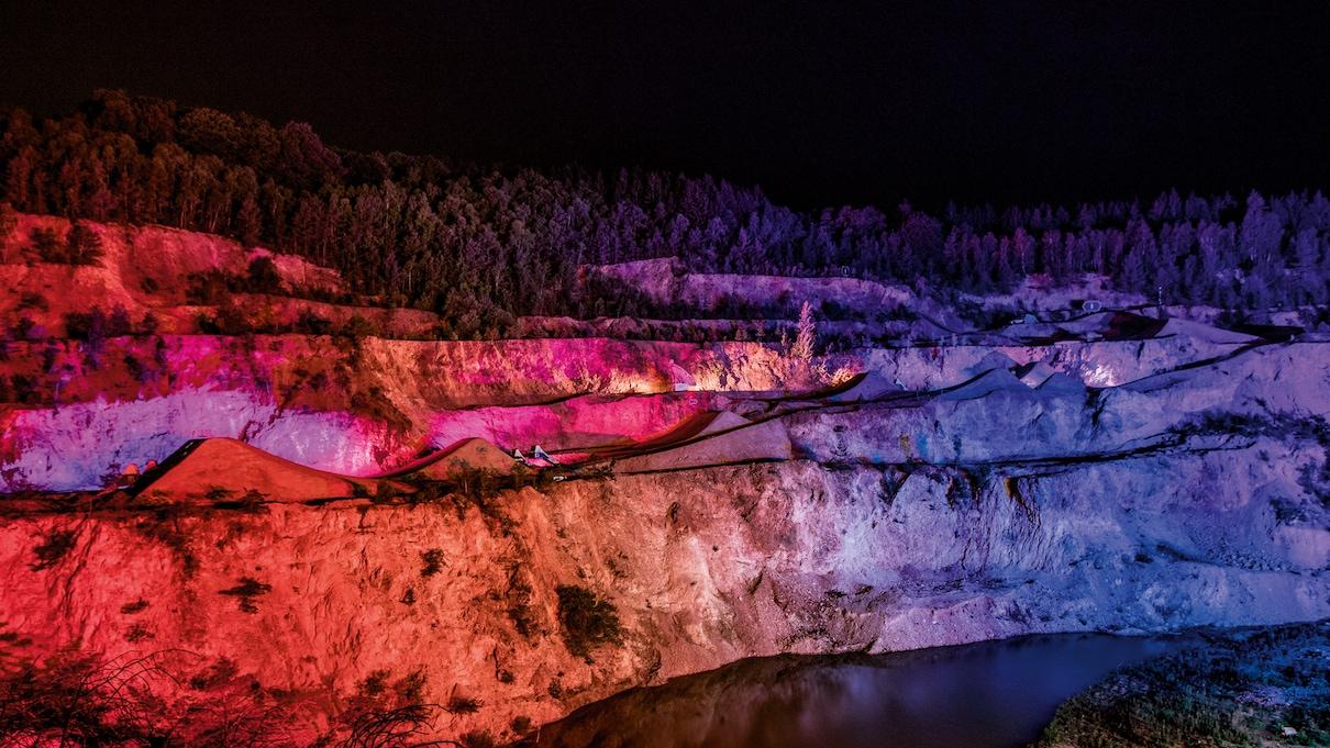 Reka, z ozadju nabrežje. Ponoči, ampak osvetljeno z rdečo in modro barvo