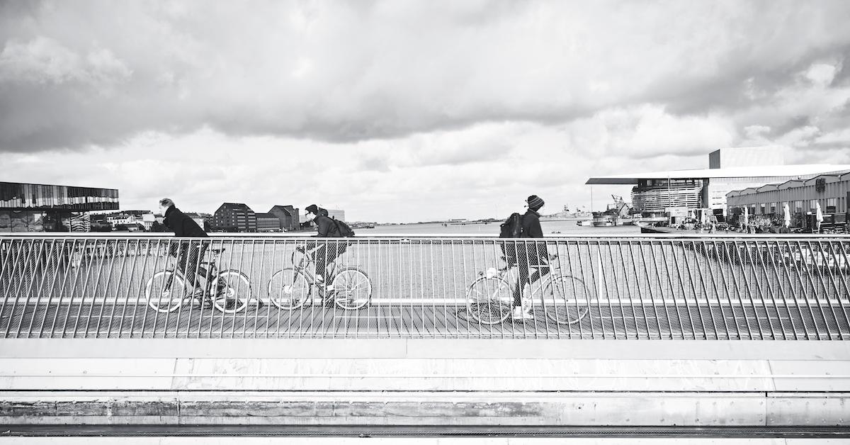 Trije kolesarji na mostu. Črno-bela slika.