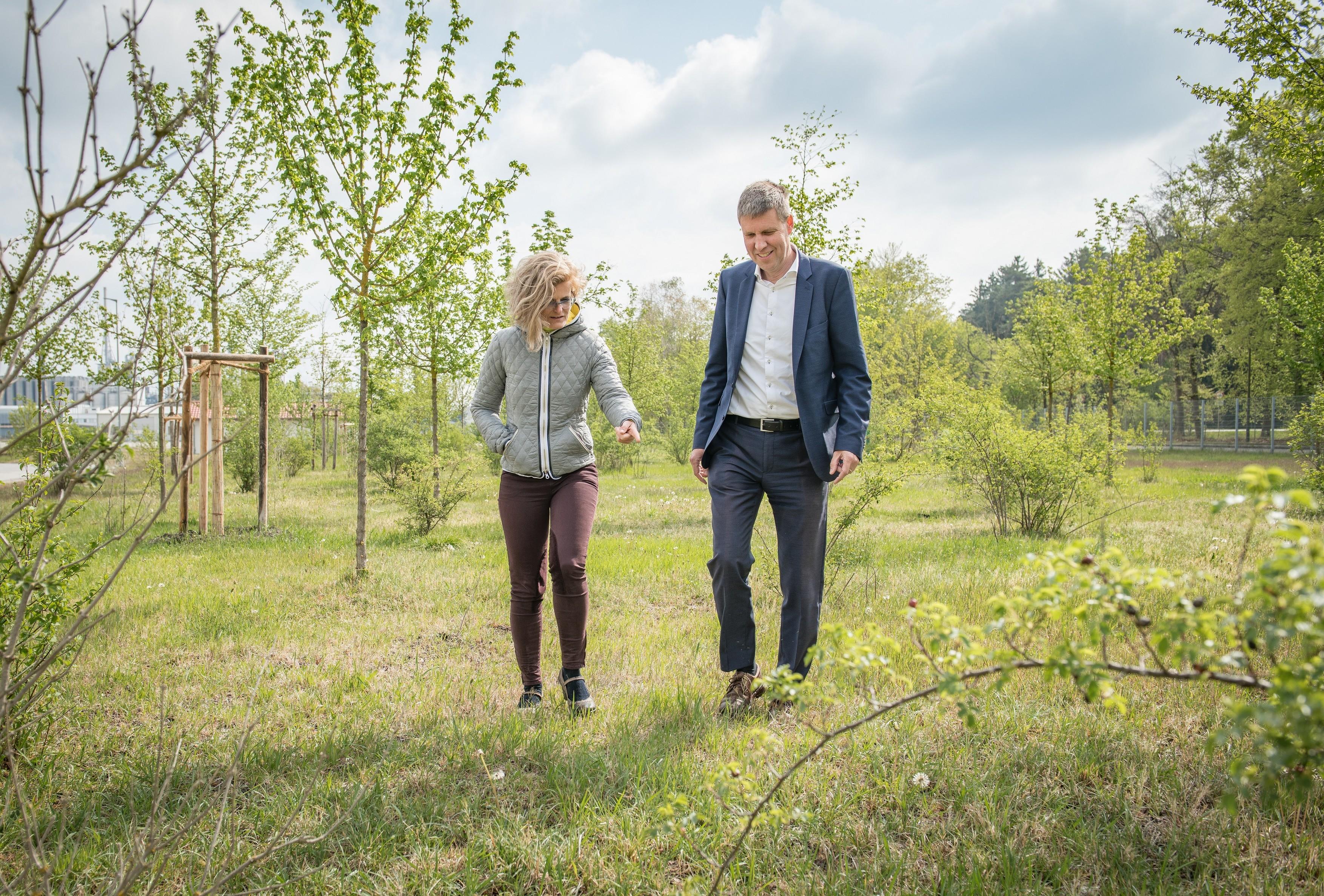 Ženska in moški, ki se sprehajata po zelenem travniku z majhnimi drevesi