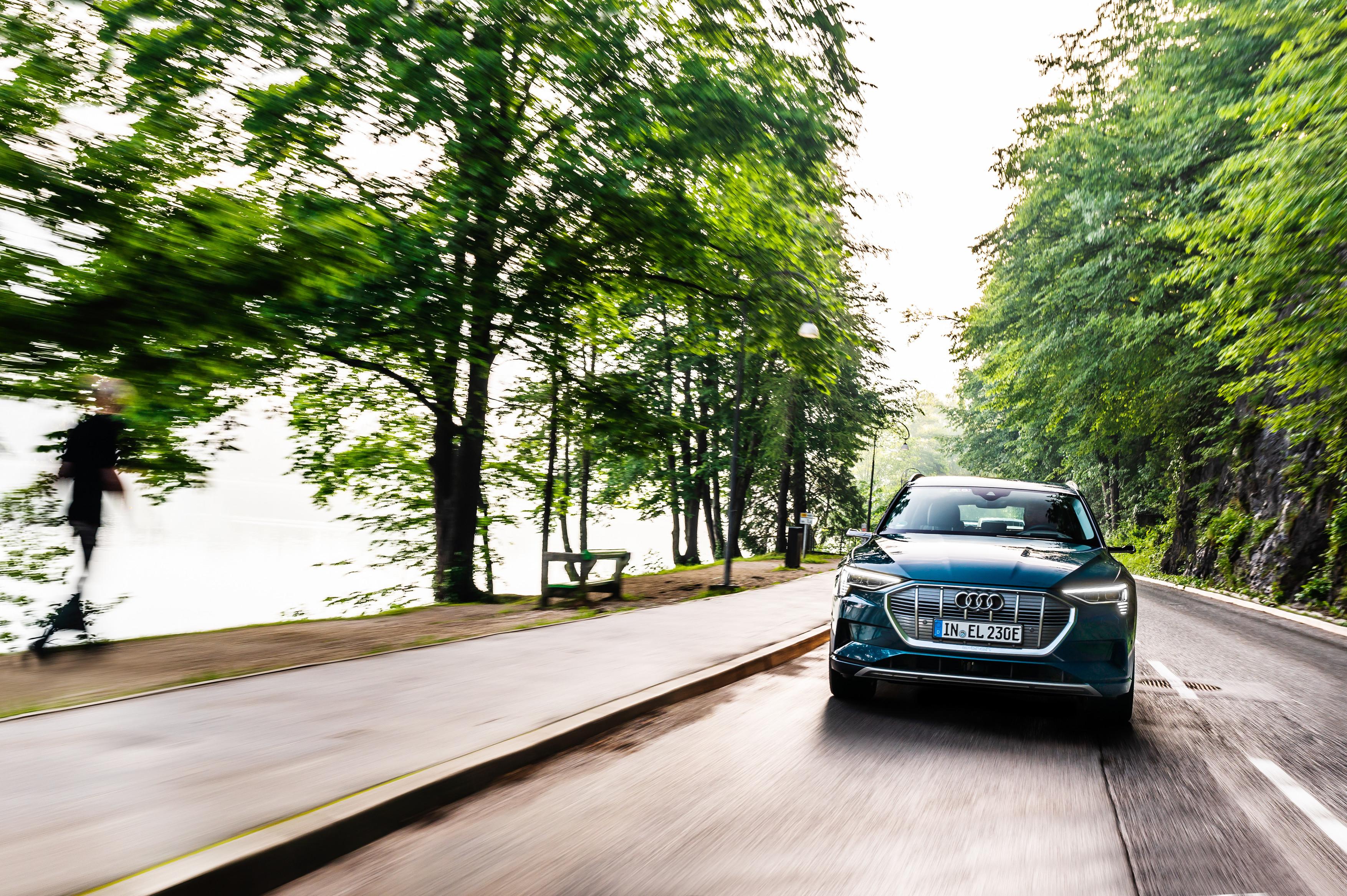Audi e-tron na cesti, ki pelje med drevoredom. Na levi strani voda