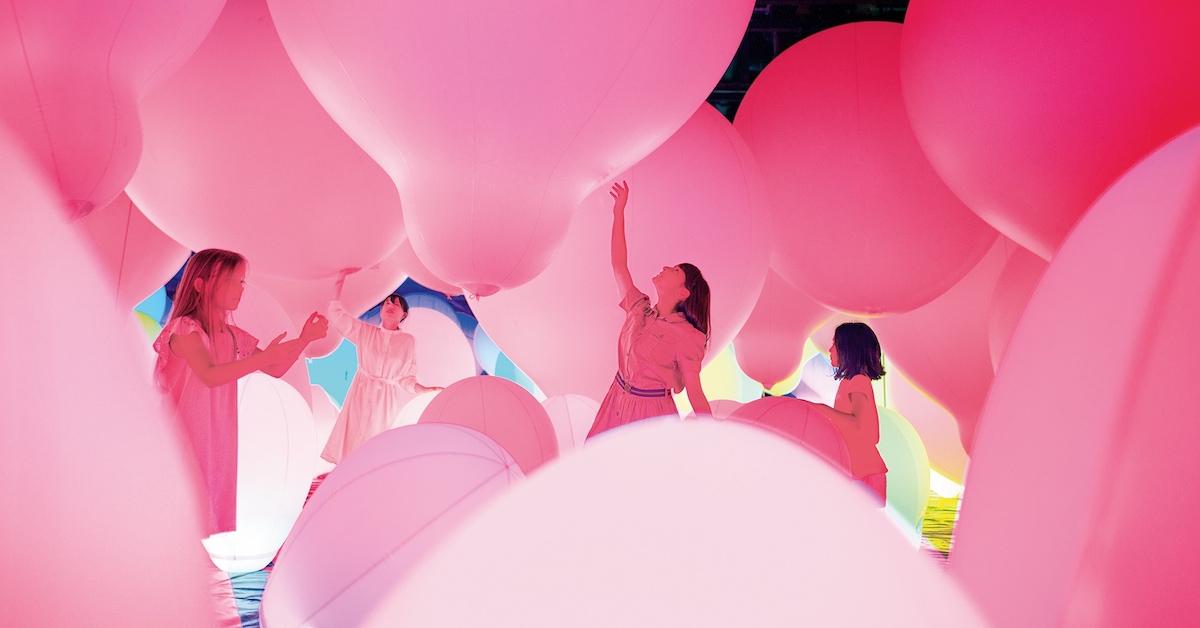Štiri ženske med igranjem z roza velikimi baloni.