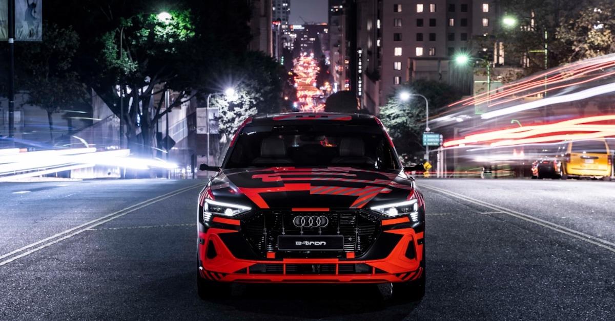 Rdeče vozilo Audi e-tron na cesti v mestu ponoči. Slikano od spredaj