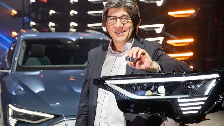Stephan Berlitz pred Audi vozilom, s LED celico v roki.