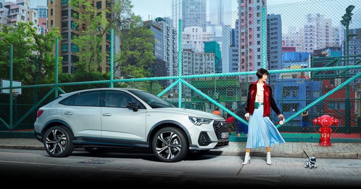 Audi terenec, pred njim ženska ki sprehaja robotskega psa. Na desni strani hidrant