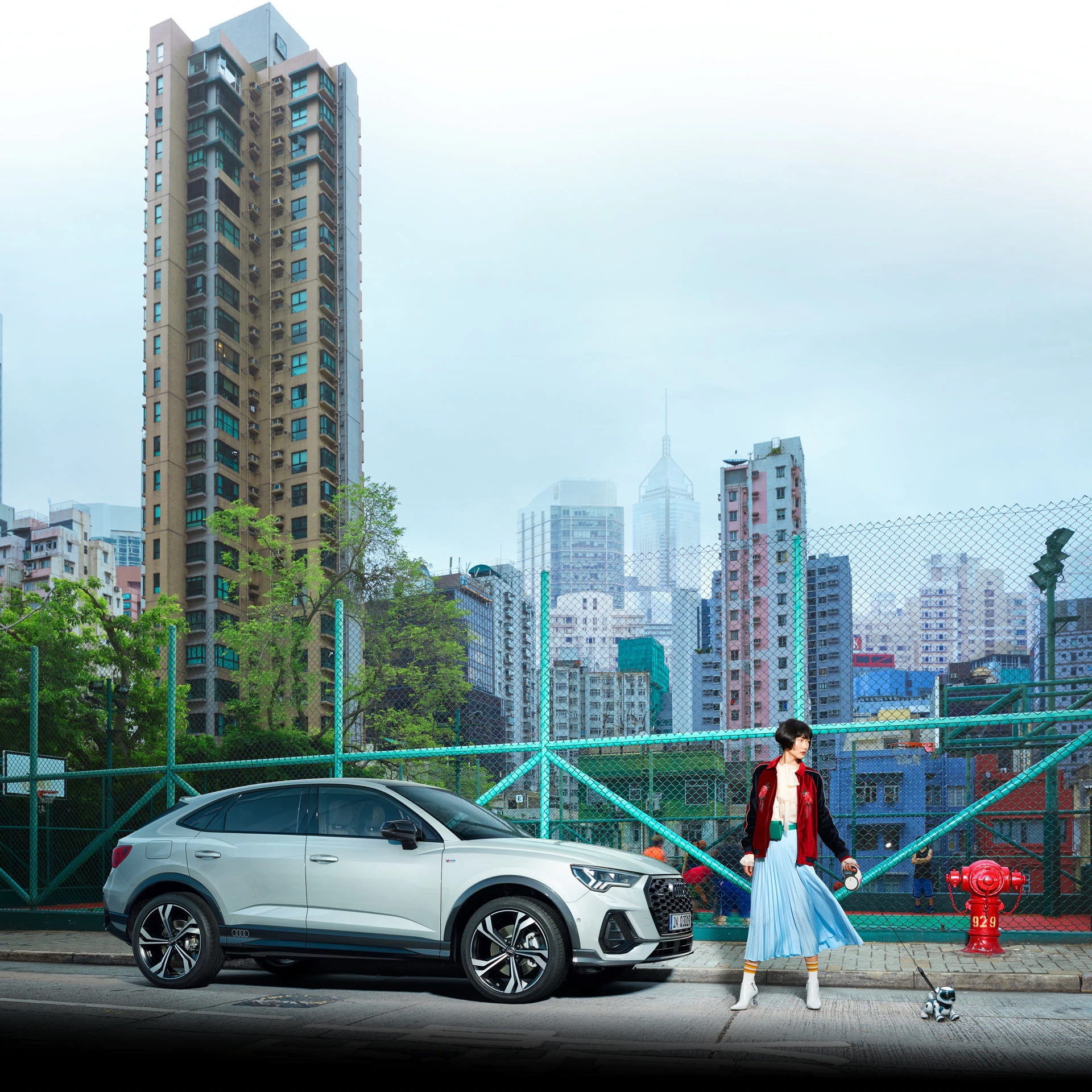 Ženska sprehaja robotskega psa. Zraven Audi e-tron, v ozadju mesto.