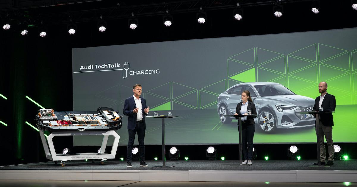 Trije predavatelji Audi Tech Talk na odru. V ozadju predstavitev, na sliki Audi e-tron sportback