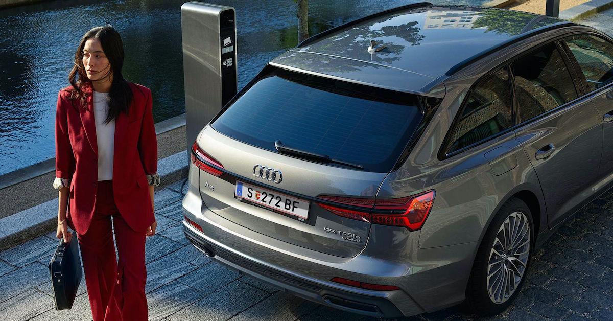 Audi A6 Avant v ozadju, v ospredju ženska v rdečem, s torbico v roki