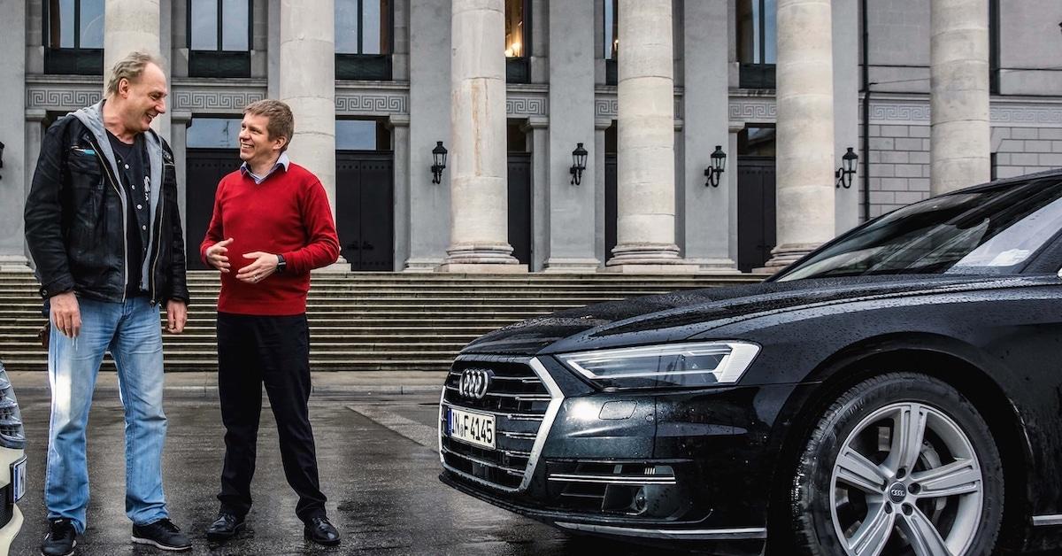 Dva moška pred Audi A8 vozilom, med pogovorom