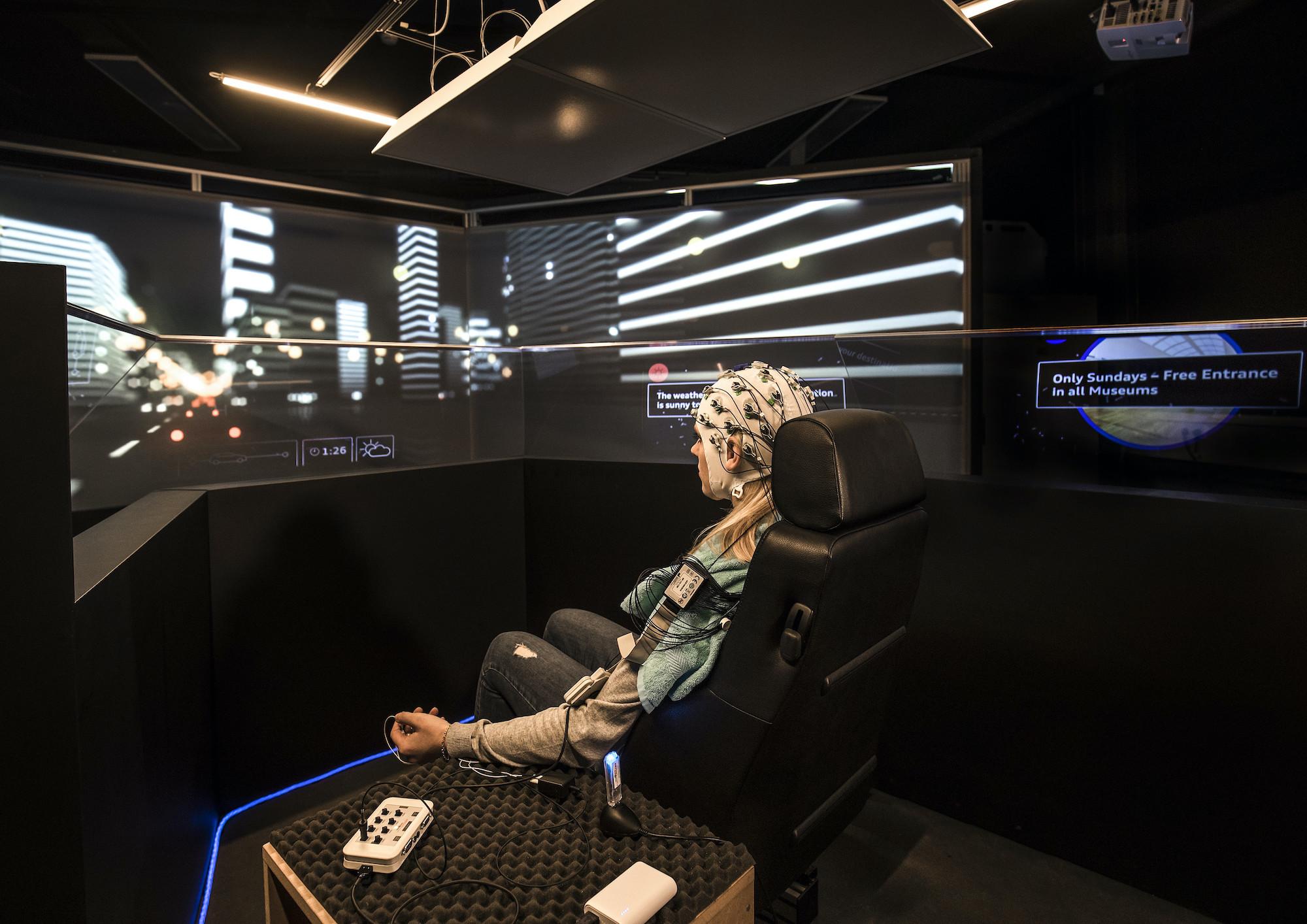Moški med testiranjem pametnega sistema Audi v simulatorju.