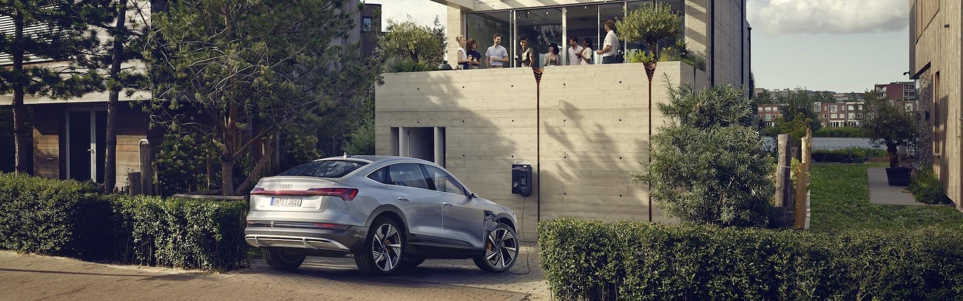 eletrični avtomobil Audi e-tron se polni pred garažo