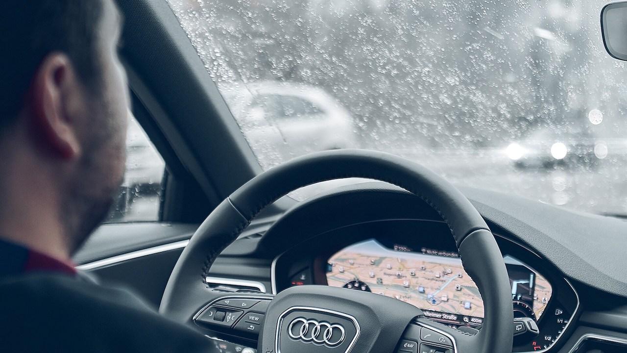 Moški vozi avto v dežju